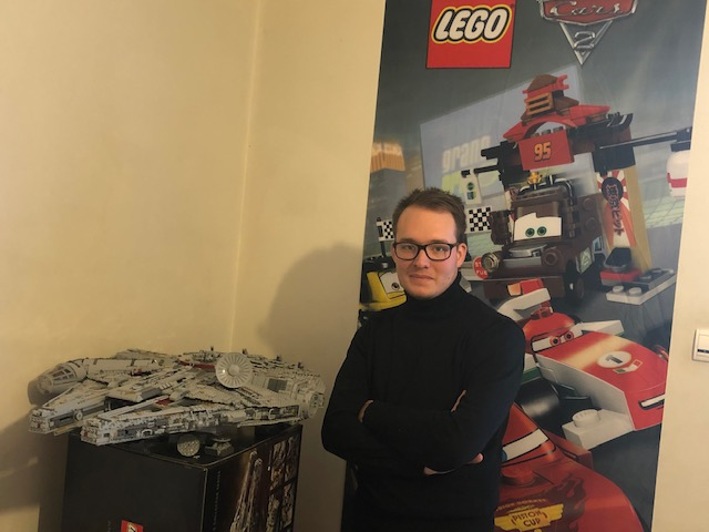Portrait of Guillaume in front of a lego poster and a Star Wars model